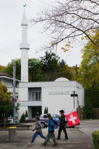 Schoolboys carrying a Swiss flag walk past the Mahmud Mosque and his minaret on October 26, 2009 in Zurich